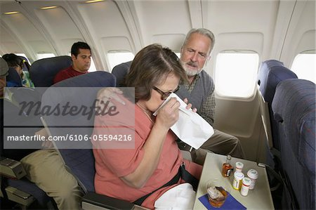 Senior Woman Vomiting Into a Sick Bag During a Flight on a Plane Stock Photo - Premium Royalty-Free, Image code: 6106-05594216