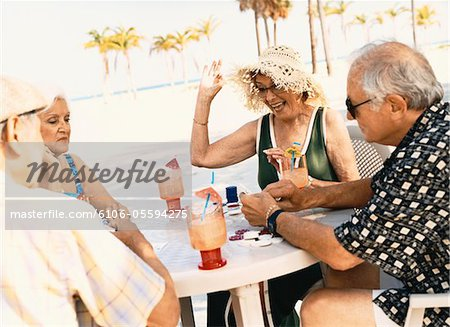 Four Senior People Playing Poker on the Beach Stock Photo - Premium Royalty-Free, Image code: 6106-05594275