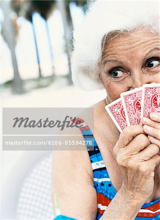 Woman Hiding Behind Her Playing Cards Stock Photo - Premium Royalty-Free, Image code: 6106-05594278