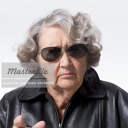portrait of an elderly caucasian woman in a leather jacket and sunglasses as she points at the camera and scowls Stock Photo - Premium Royalty-Free, Image code: 6106-05596078