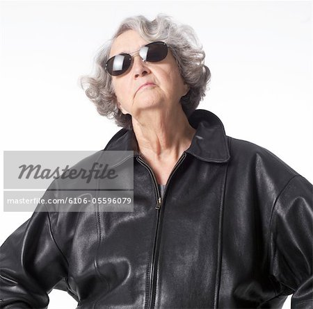 portrait of an elderly caucasian woman in a leather jacket and sunglasses as she throws her head back confidently Stock Photo - Premium Royalty-Free, Image code: 6106-05596079