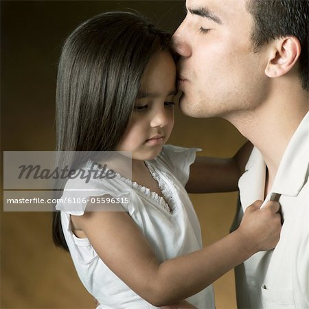 studio portrait of an ethnic father giving his young daughter a kiss on the forehead