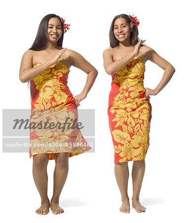 two polynesian teenage sisters in orange floral dresses do a traditional dance Stock Photo - Premium Royalty-Free, Image code: 6106-05596460