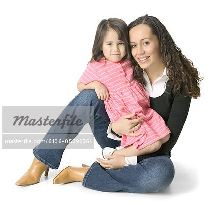 a young ethnic woman sits with her little sister on her lap Stock Photo - Premium Royalty-Free, Image code: 6106-05596561