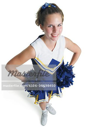 a teenage caucasian female cheerleader holds pom poms and smiles as she looks up at the camera Stock Photo - Premium Royalty-Free, Image code: 6106-05598450