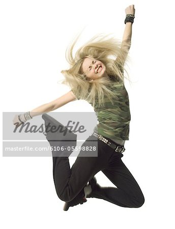 a blonde female teen in black pants and a camouflage shirt jumps up wildly Stock Photo - Premium Royalty-Free, Image code: 6106-05598828