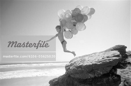 Boy with a Bunch of Balloons Jumping Off of a Rock Stock Photo - Premium Royalty-Free, Image code: 6106-05625020