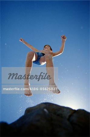 Child Jumping Off of a Rock Stock Photo - Premium Royalty-Free, Image code: 6106-05625027