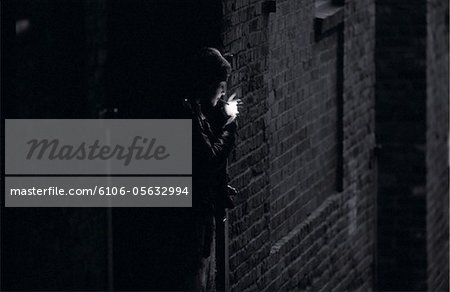Teenage girl (15-17) lighting cigarette in alley (B&W) Stock Photo - Premium Royalty-Free, Image code: 6106-05632994