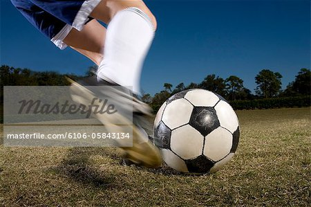 Young woman kicking soccer ball, low section (blurred motion) Stock Photo - Premium Royalty-Free, Image code: 6106-05843134