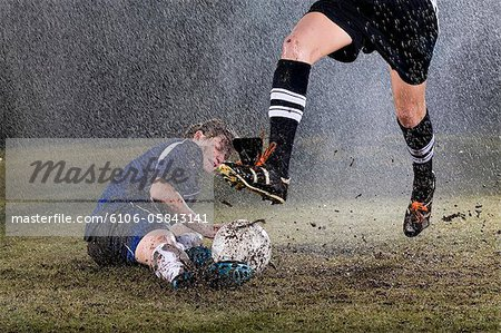 Two young women playing soccer in rain Stock Photo - Premium Royalty-Free, Image code: 6106-05843141