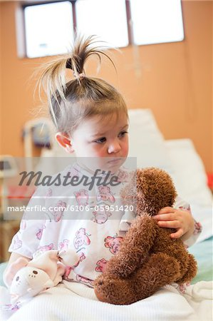 Toddler girl in hospital bed holding toy bear. Stock Photo - Premium Royalty-Free, Image code: 6106-05951420