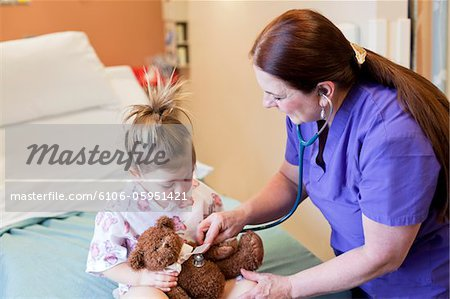 Nurse taking care of toddler girl in hospital. Stock Photo - Premium Royalty-Free, Image code: 6106-05951421