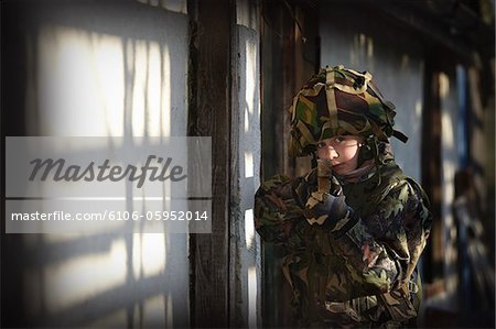 Young boy dressed as soldier aiming wooden gun Stock Photo - Premium Royalty-Free, Image code: 6106-05952014