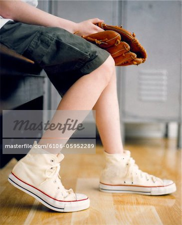 boy legs with tennis shoes holding baseball mitt Stock Photo - Premium Royalty-Free, Image code: 6106-05952289