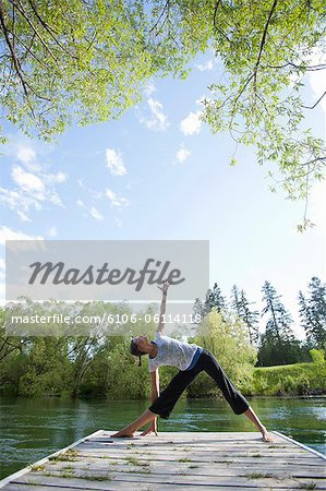 Woman practicing yoga on dock Stock Photo - Premium Royalty-Free, Image code: 6106-06114118