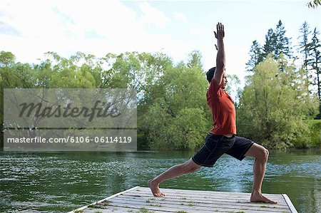 Man stretching on dock Stock Photo - Premium Royalty-Free, Image code: 6106-06114119