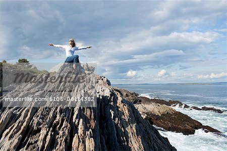 Woman outstretches arms by oceanside. Stock Photo - Premium Royalty-Free, Image code: 6106-06114382