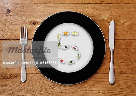 Plate with fruit pills forming a 5 Stock Photo - Premium Royalty-Free, Image code: 6106-06165553