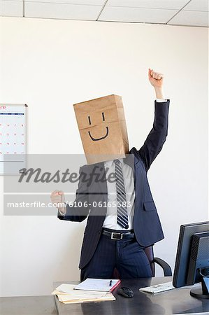 Businessmann wearing paper bag on head smiling Stock Photo - Premium Royalty-Free, Image code: 6106-06165583