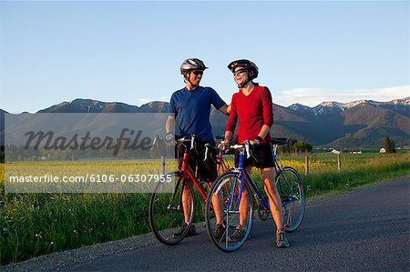 Cyclist couple laughing while enjoying scenic view Stock Photo - Premium Royalty-Free, Image code: 6106-06307955