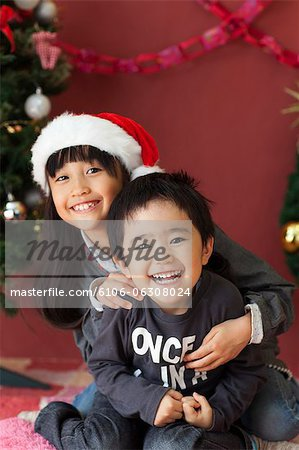Brother and sister play joyfully at Christmas. Stock Photo - Premium Royalty-Free, Image code: 6106-06308024