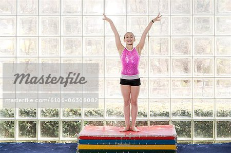 young gymnast holding hands in air, smiling Stock Photo - Premium Royalty-Free, Image code: 6106-06308082