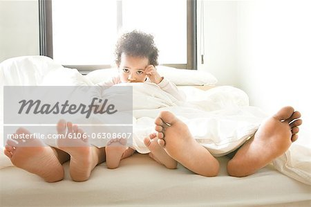 Low section of family lying on bed. Stock Photo - Premium Royalty-Free, Image code: 6106-06308607