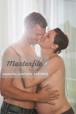 Pregnant woman and man embracing Stock Photo - Premium Royalty-Free, Image code: 6106-06308931