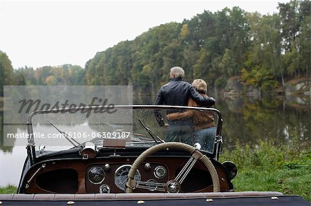 Senior couple looking at lake, in front of antique car Stock Photo - Premium Royalty-Free, Image code: 6106-06309187