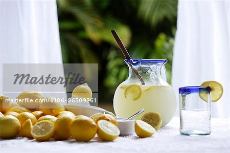 Pitcher of lemonade, glass, lemons on table in kitchen window Stock Photo - Premium Royalty-Free, Image code: 6106-06309261