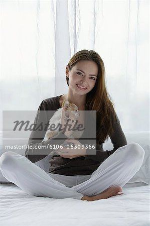 Young woman holding puppy Stock Photo - Premium Royalty-Free, Image code: 6106-06309366