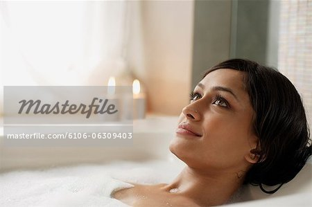 Woman reclining in bathtub Stock Photo - Premium Royalty-Free, Image code: 6106-06309403