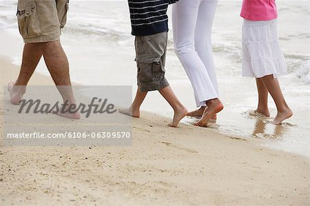 feet of family walking on beach Stock Photo - Premium Royalty-Free, Image code: 6106-06309570