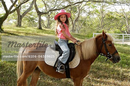 Young girl riding pony Stock Photo - Premium Royalty-Free, Image code: 6106-06309625