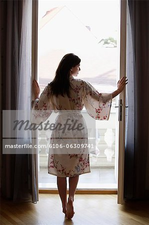 young woman standing at open doorway Stock Photo - Premium Royalty-Free, Image code: 6106-06309741