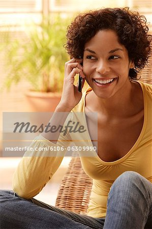 Woman talking on phone and smiling. Stock Photo - Premium Royalty-Free, Image code: 6106-06309990