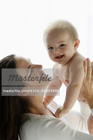 mother looking at baby and smiling Stock Photo - Premium Royalty-Free, Image code: 6106-06309995