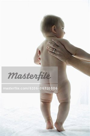 mother holding naked baby Stock Photo - Premium Royalty-Free, Image code: 6106-06310006