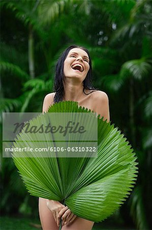 naked woman behind big tropical leaf Stock Photo - Premium Royalty-Free, Image code: 6106-06310322