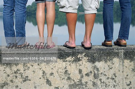 legs of teens standing on wall near lake Stock Photo - Premium Royalty-Free, Image code: 6106-06310676