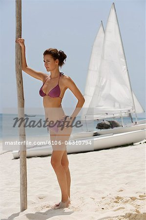 woman standing in front of sail boat Stock Photo - Premium Royalty-Free, Image code: 6106-06310794
