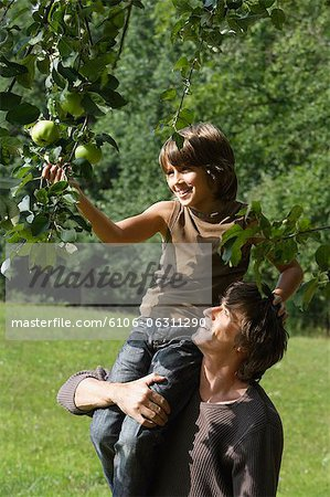 father holding son up to pick apple from tree Stock Photo - Premium Royalty-Free, Image code: 6106-06311290