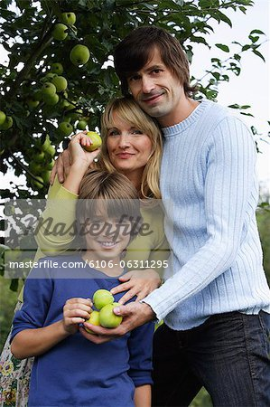 family under apple tree Stock Photo - Premium Royalty-Free, Image code: 6106-06311295