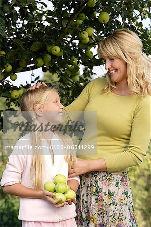 mother and daughter under apple tree Stock Photo - Premium Royalty-Free, Image code: 6106-06311299