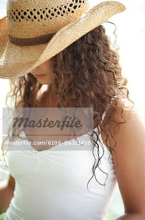 Woman wearing straw hat, looking down Stock Photo - Premium Royalty-Free, Image code: 6106-06311450