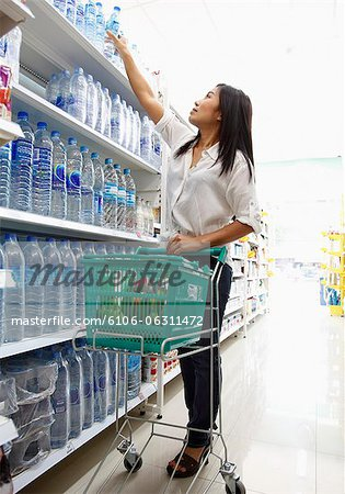 Woman reaching for product in supermarket Stock Photo - Premium Royalty-Free, Image code: 6106-06311472