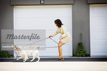 Woman tangled up in her dog's leashes Stock Photo - Premium Royalty-Free, Image code: 6106-06335170