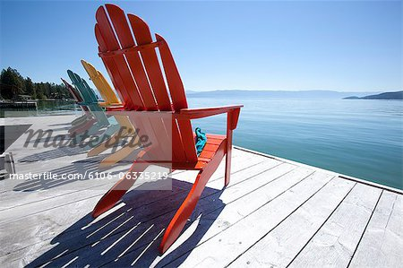 Row of adirondak chairs on dock by scenic lake Stock Photo - Premium Royalty-Free, Image code: 6106-06335219