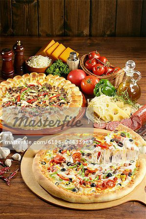 Lifting slice of pizza with ingredients Stock Photo - Premium Royalty-Free, Image code: 6106-06433909